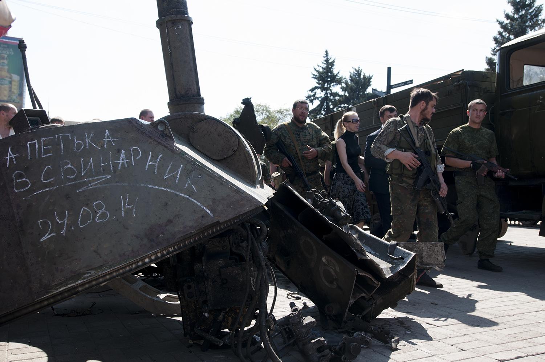 Separatists soldiers walking between the displayed Ukrainian vehicules
