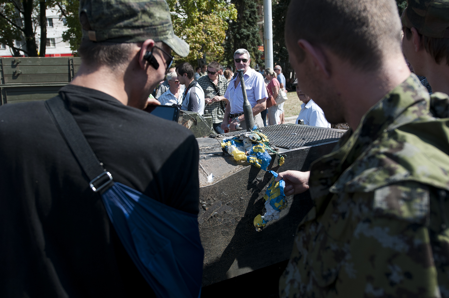 Man looking at three separatists solider who are laughing at the view of burned Ukrainian flag