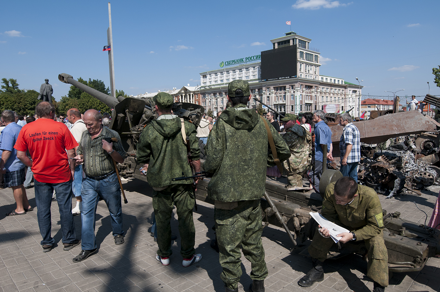 DNR soldier reading the newspaper as his comrades patrol Lenin Square