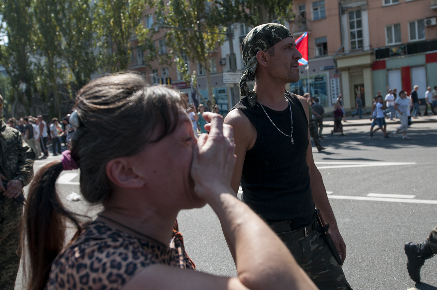 A separatist carrying a smirk on his face as the POW walk passed him and a woman cries while insulting them