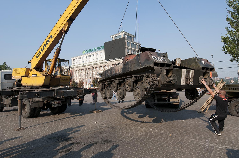 A man pulling onto a destroyed Ukrainian APC