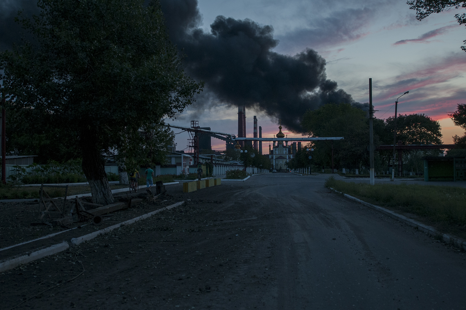 Dark smoke rising over church 19 as the sunset down