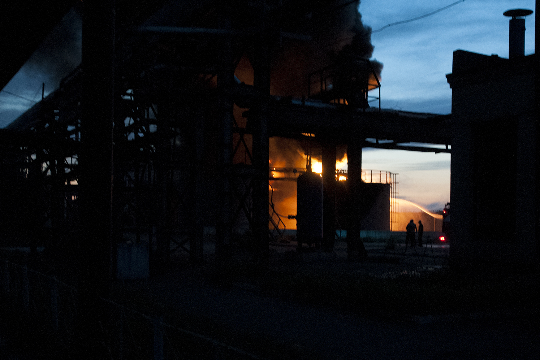Fireman fighting against a burning oil tank