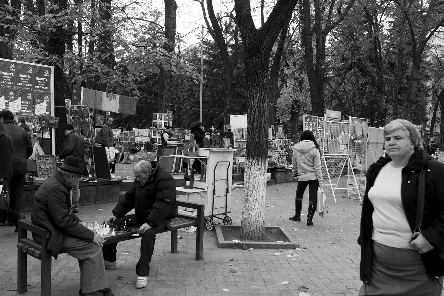 Old men playing chess on bench in fornt of the souvenir market