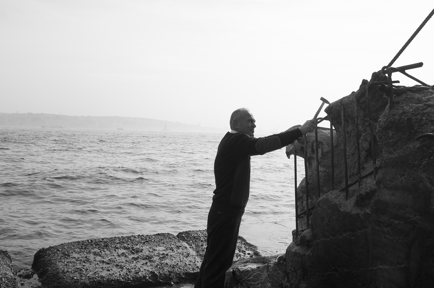 Artist sculpting an eagle in a reinforced concrete block on the  Bosphorus strait side.