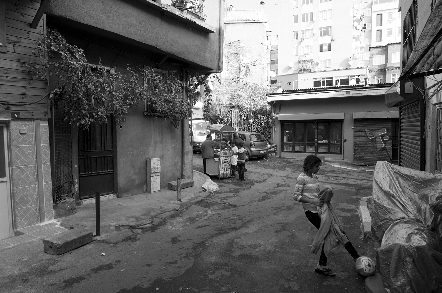 Young girl playing with a football while younger children buy candies from a small kiosk inside  Beyoğlu district