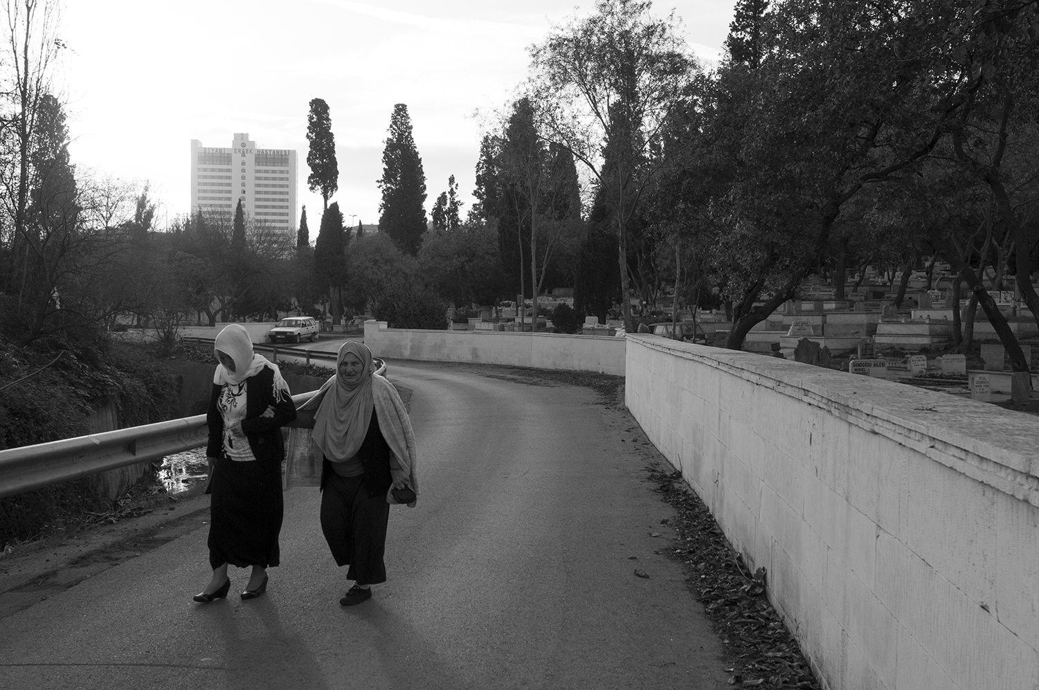 Two women walking though Karacaahmet Cemetery