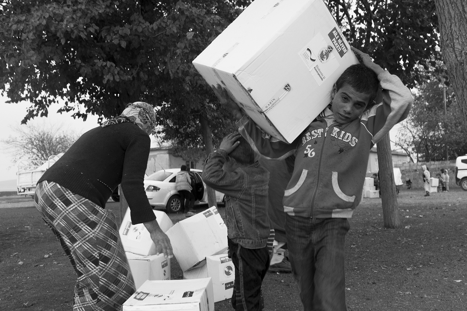 Young Syrian boys helping their mother to bring back the relief package to their tent.