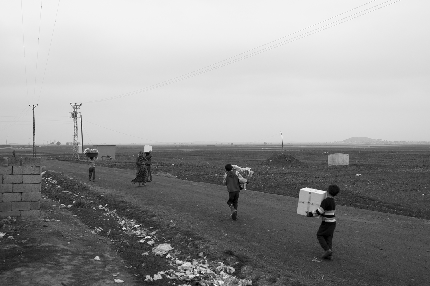 Syrian childrencarrying aid boxes and blanket to their tents;