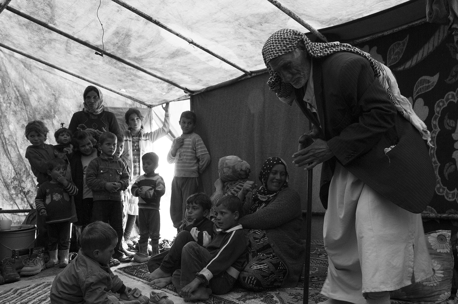 """""""Baram"""" next to his 9 months pregnant wife, his children and the membersof two other families staying in the tents next to his."""
