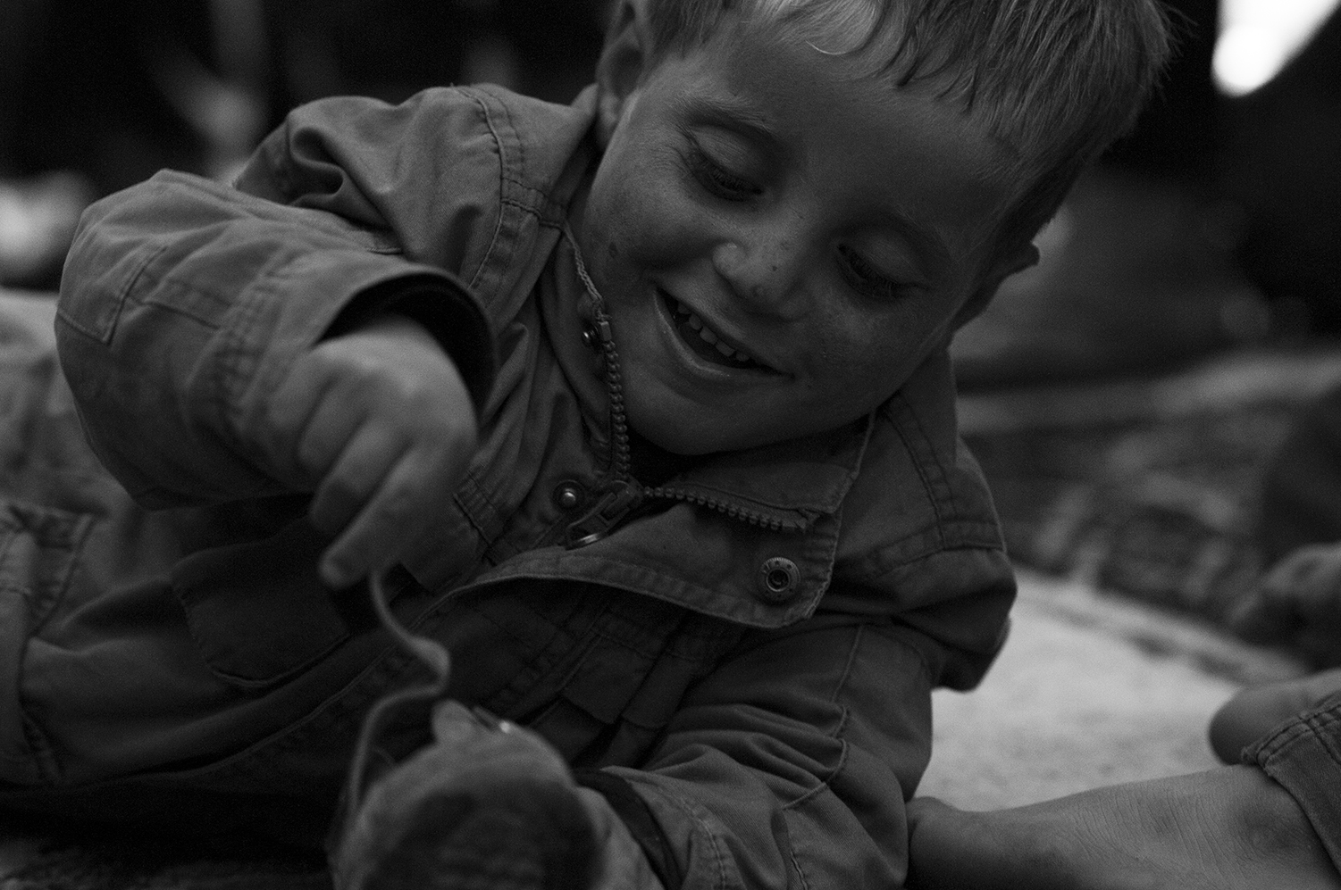 """Young child playing with one of his shoe in """"Baram"""" family."""