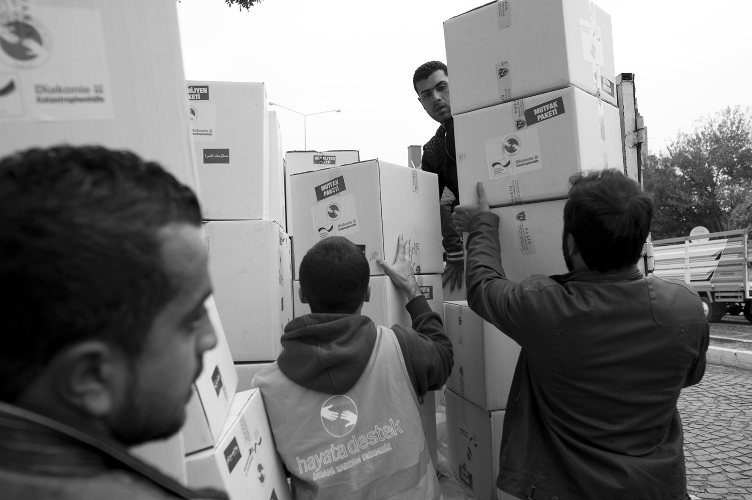 Volunteers and Hayata Destek workers finish loading a truck with aid boxes which are designated for Syrians living outside of the refugee camps around Suruç.
