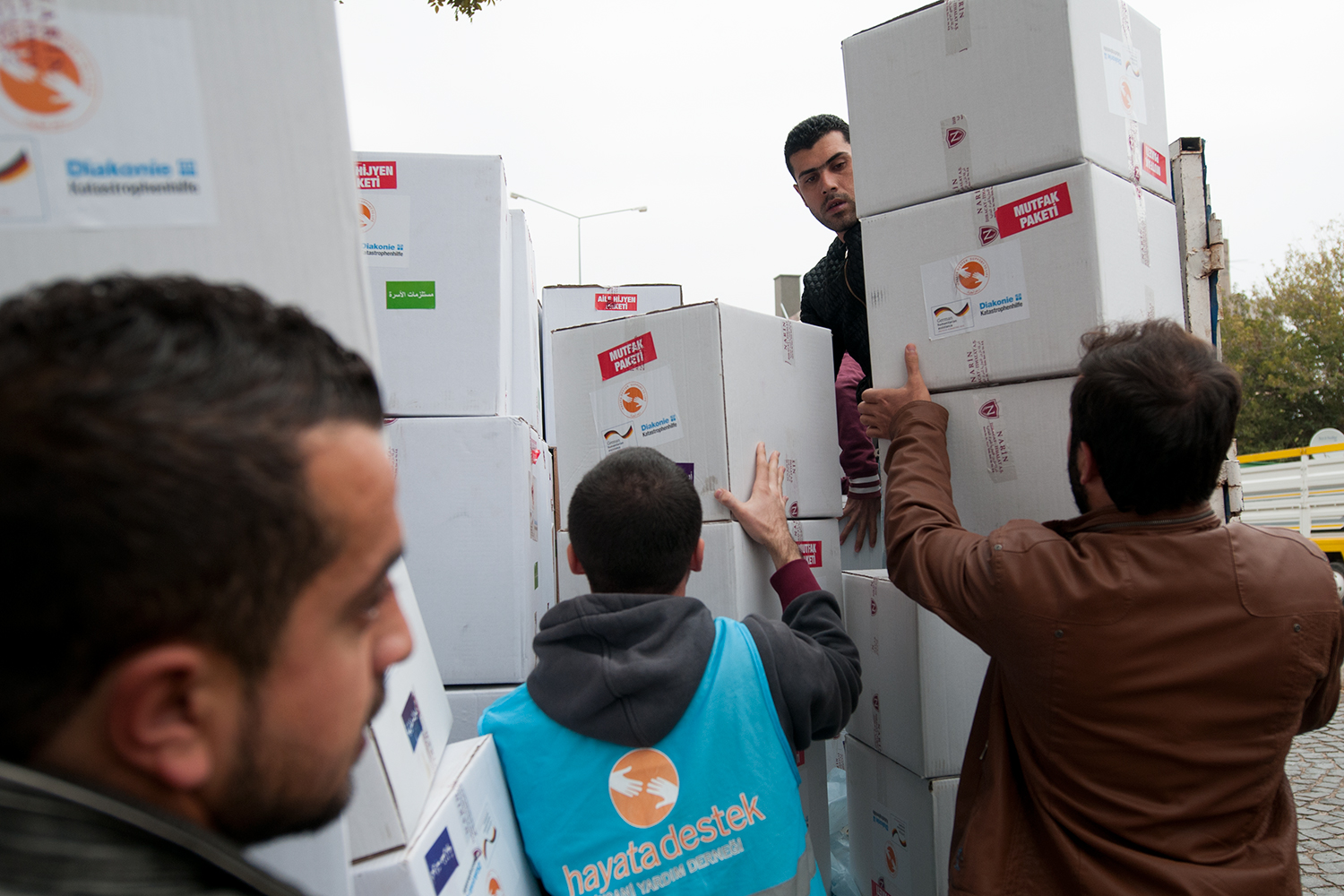 Volunteers from Hayat Destek loading into a truck relief packages before delivering them to Syrian refugees