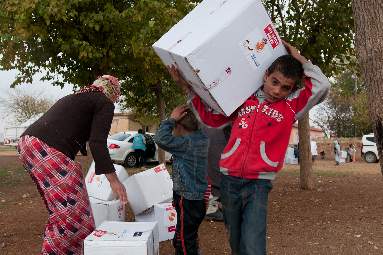 Kurdish kid helping his mother bringing the relief packages to their tent