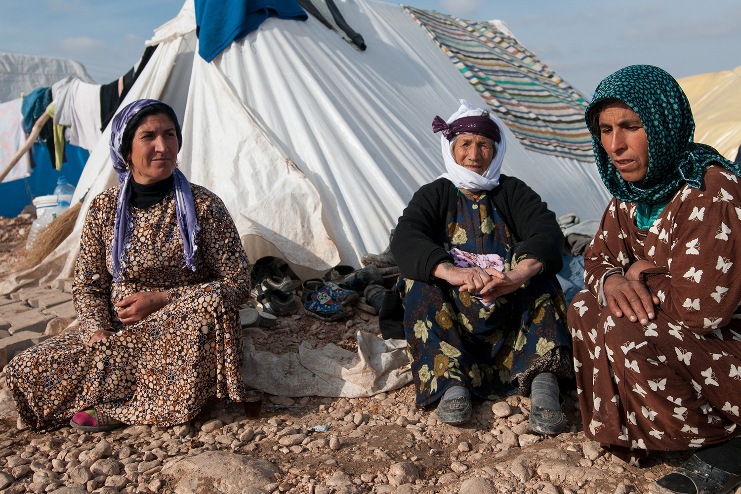 Syrian women sitting in front of their tent in a refugee camp near suruç