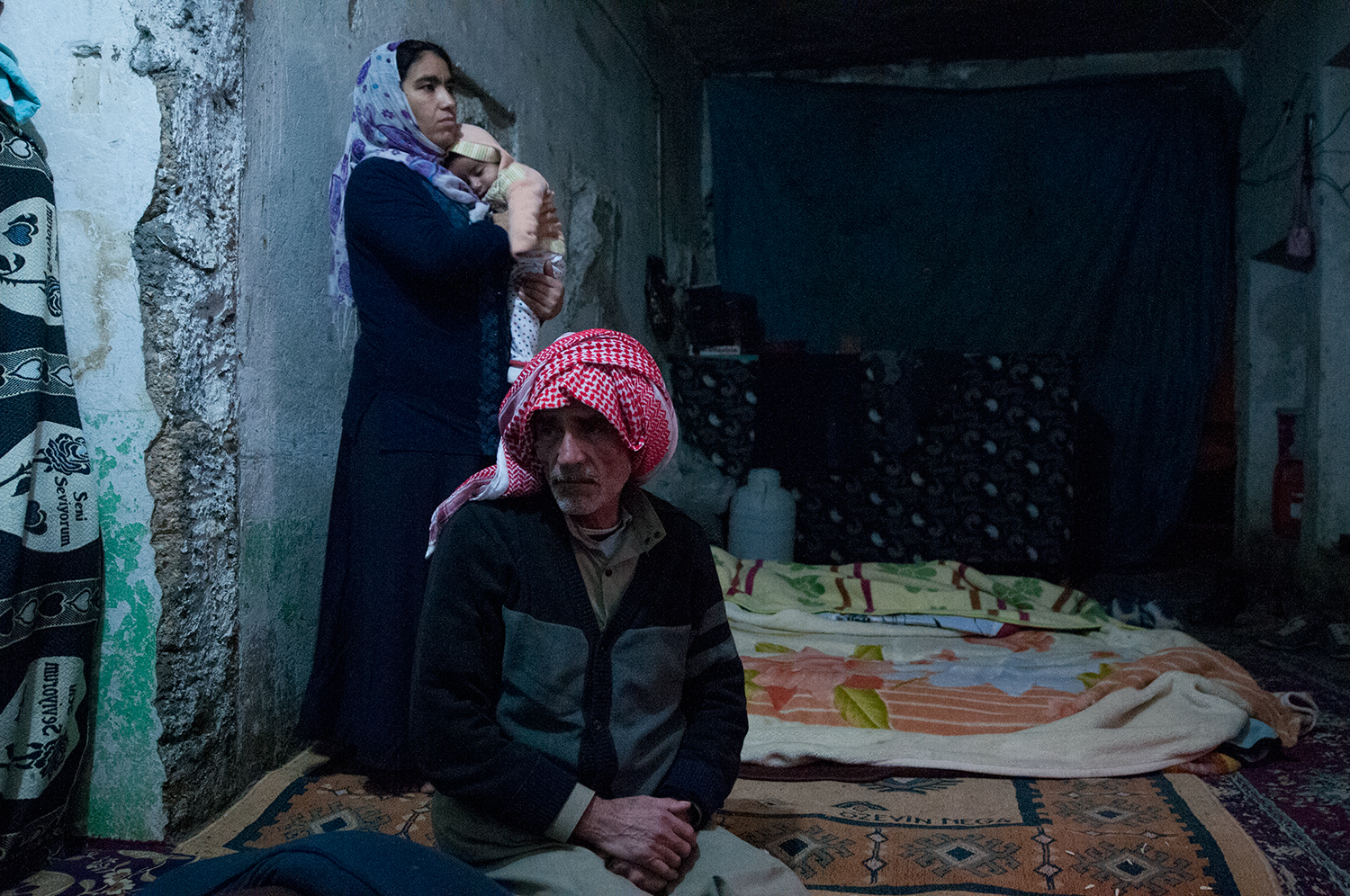 A Kurdish family from Syria living in a storage unit that they are renting in Suruç