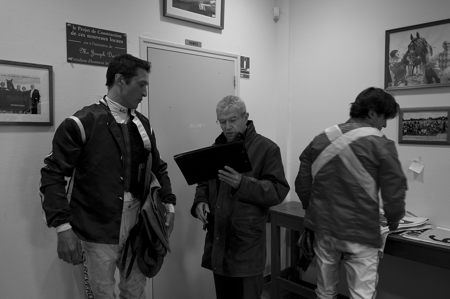 Jockeys at the weight-in supervised by a race steward.