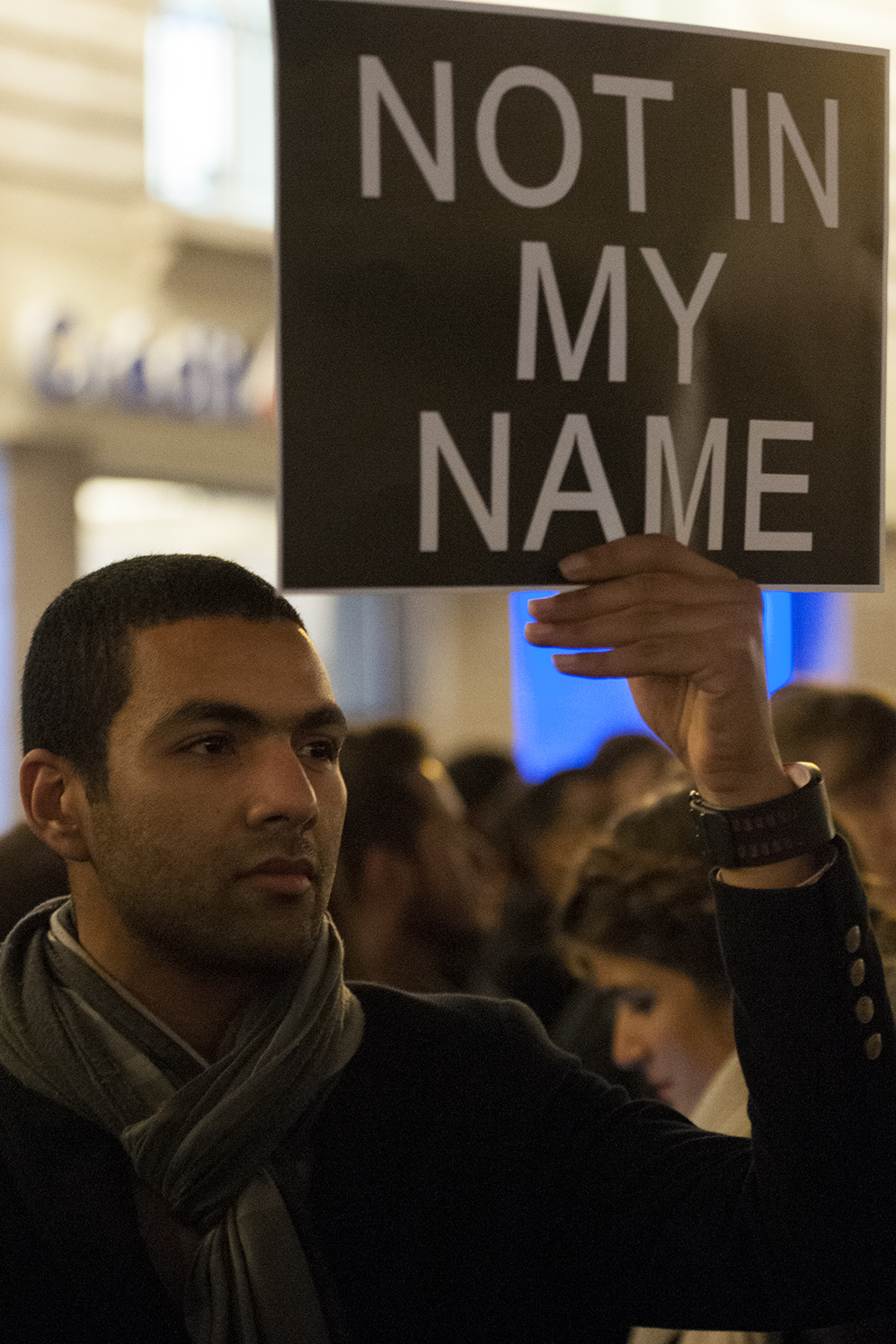 A man holding a sign denouncing the terrorist attack against Charlie Hebdo