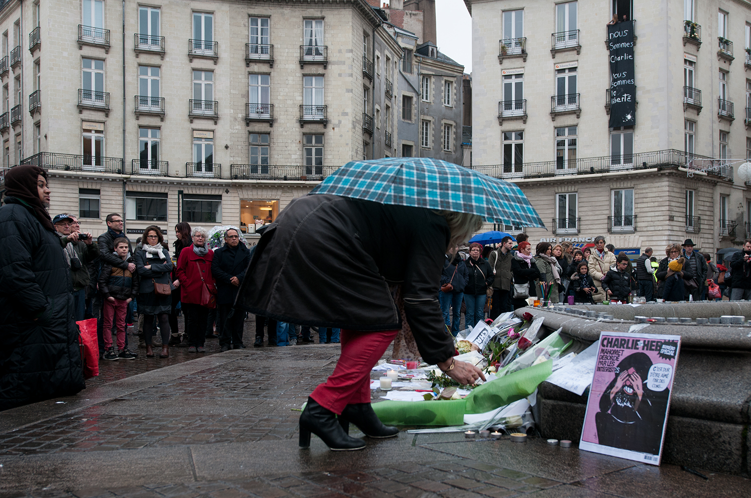 """A woman putting a candle on the ground in memories of the 17victims who lost their life between the 7th and 9th January 2014. Front page of a Charlie Hebdo published in February 2006 """"Mohamed overwhelmedby fundamentalist"""" """"It is hard to be loved by morons"""". The banner hanging from the window """"We are all Charlie. We are all the liberty"""""""