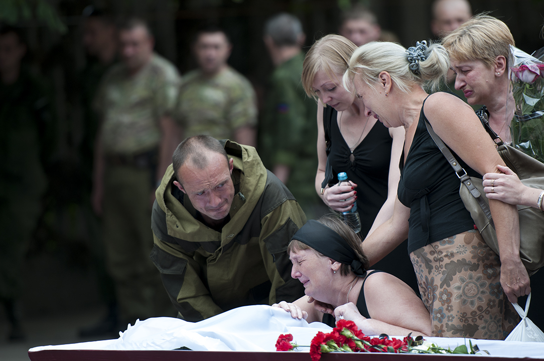 Mother crying over the open coffin of her son during the military ceremony in the training camp of the battalion.