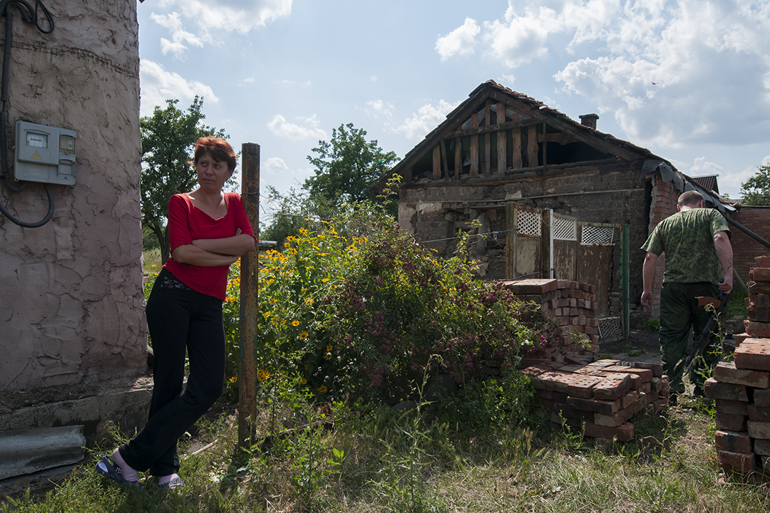 Woman standing next to her house as Aleksei walks towards the front line position hold by his men