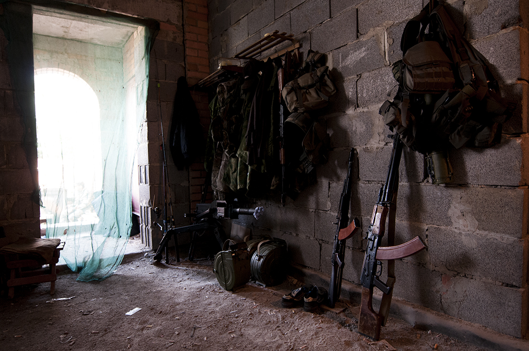 Fishing rob standing behind a grenade launcher and other military gear in the Patriot Battalion base located on the front line