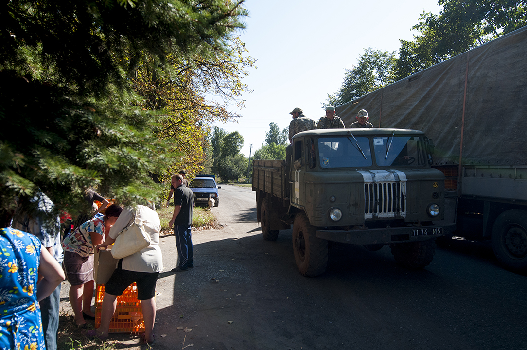 Ukrainian soldiers ridding on a millitary truck as villagers collect their chickens in Klynove