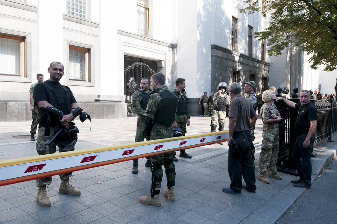 Members of the National Guard smiling as an old man yell at them in from of the Rada an hour and a half aft er the explosion that killed three and injured over 90.