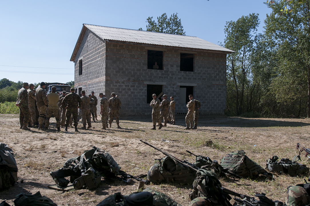 Ukrainian and U.S. soldiers discussing about tactics to use while taking assault on buildings.