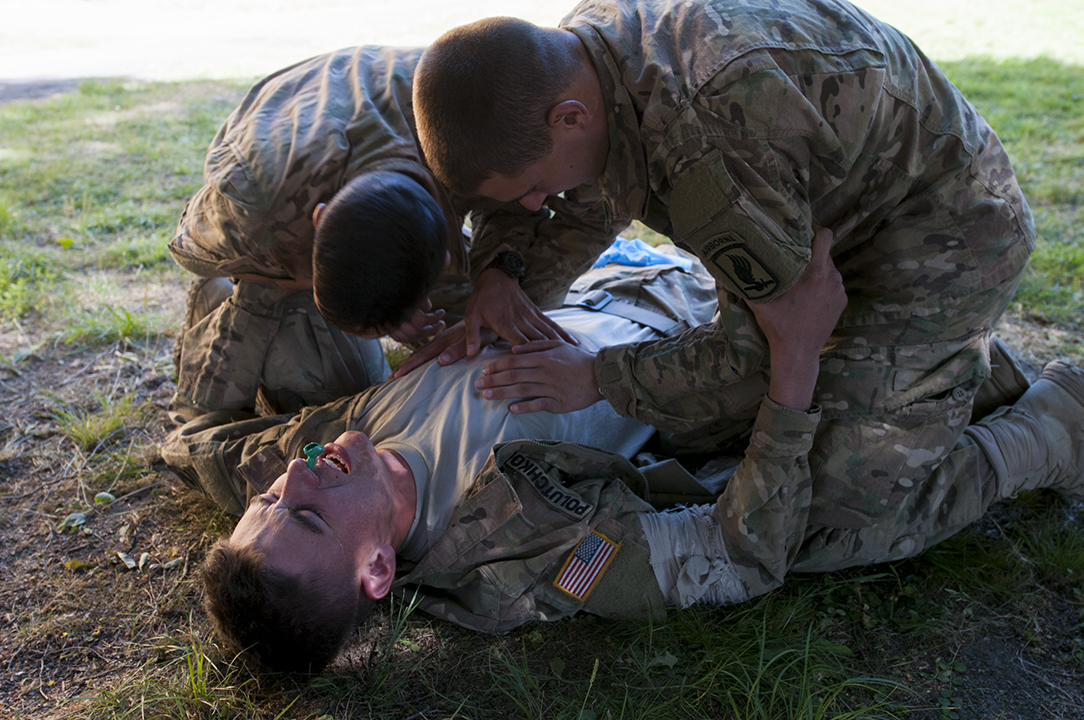 Paratroopers inspecting the chest of their comrade during medical training.