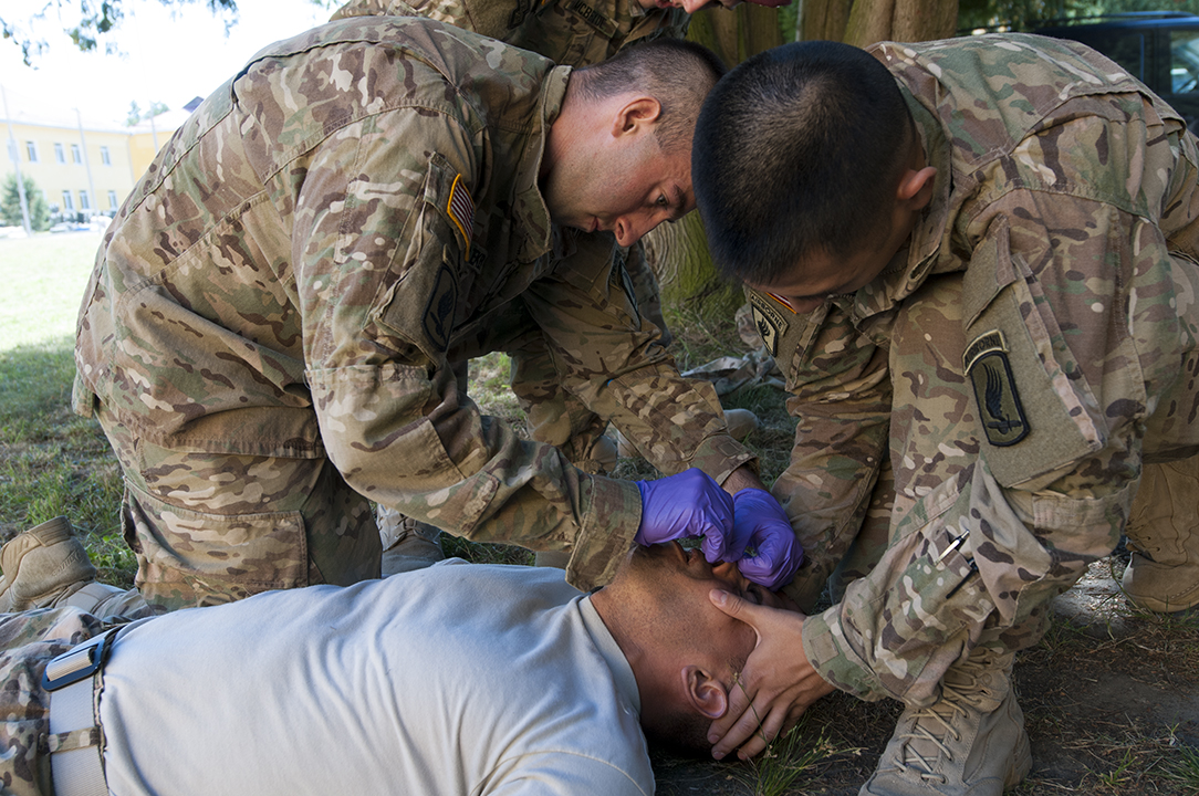 U.S. soldiers sliding a  nasal trumpet inside the nose of their comrade during medical training.