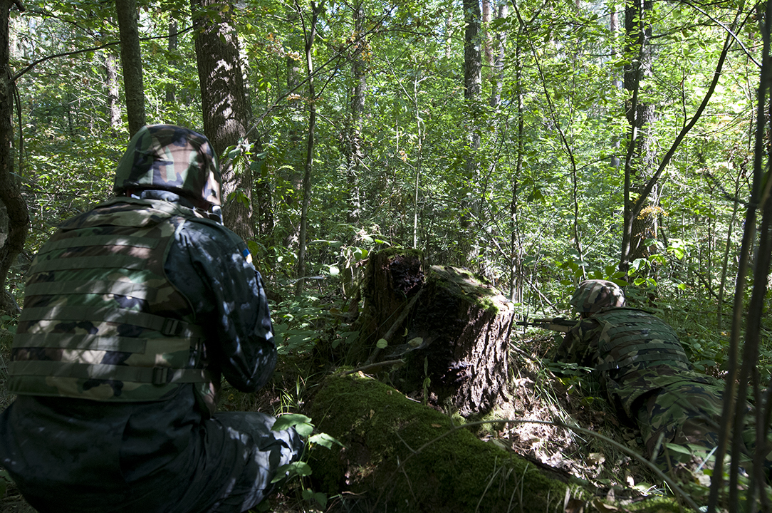 Ukrainian soldiers returning fire from behind cover as they slowly progress inside the forest.