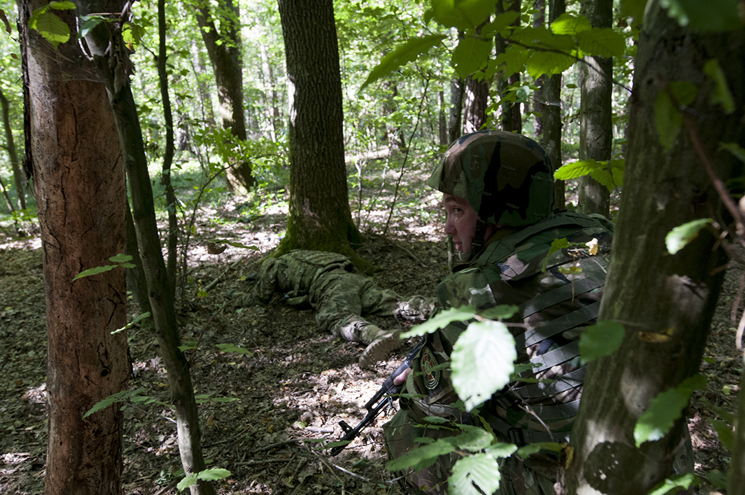 Ukrainian soldier guarding one of his U.S. counterpart playing dead during exercise.