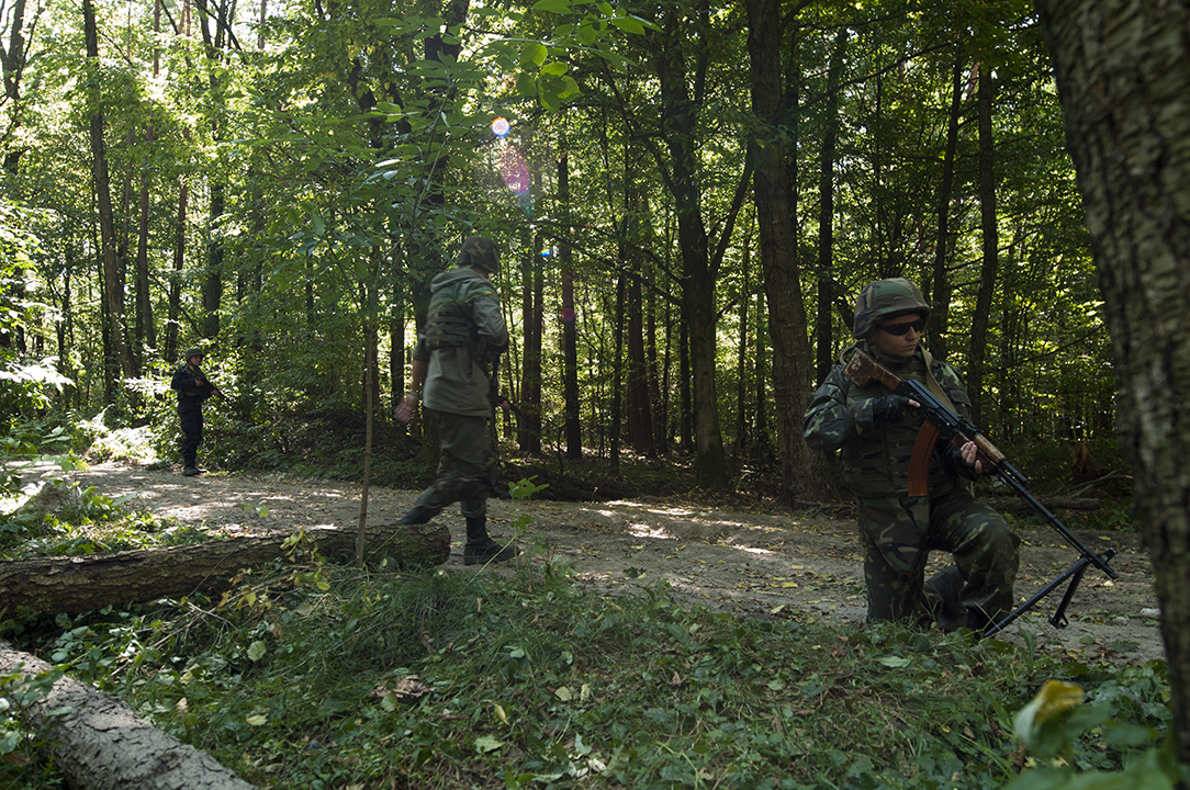 Ukrainian soldiers from the national guard returning to their patrol path after successfully defeating  an ambush during their training exercise.