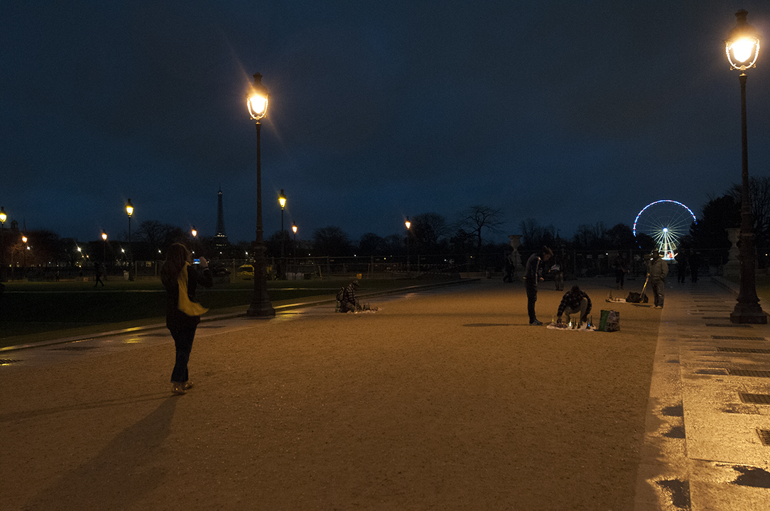 The unilluminated Eiffel Tower detaching itself  from the landscape  as a woman take pictures of street hawkers.