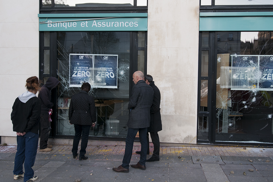 People assessing the damages made by rioters against a bank and insurance agency from the Crédit Agricole.