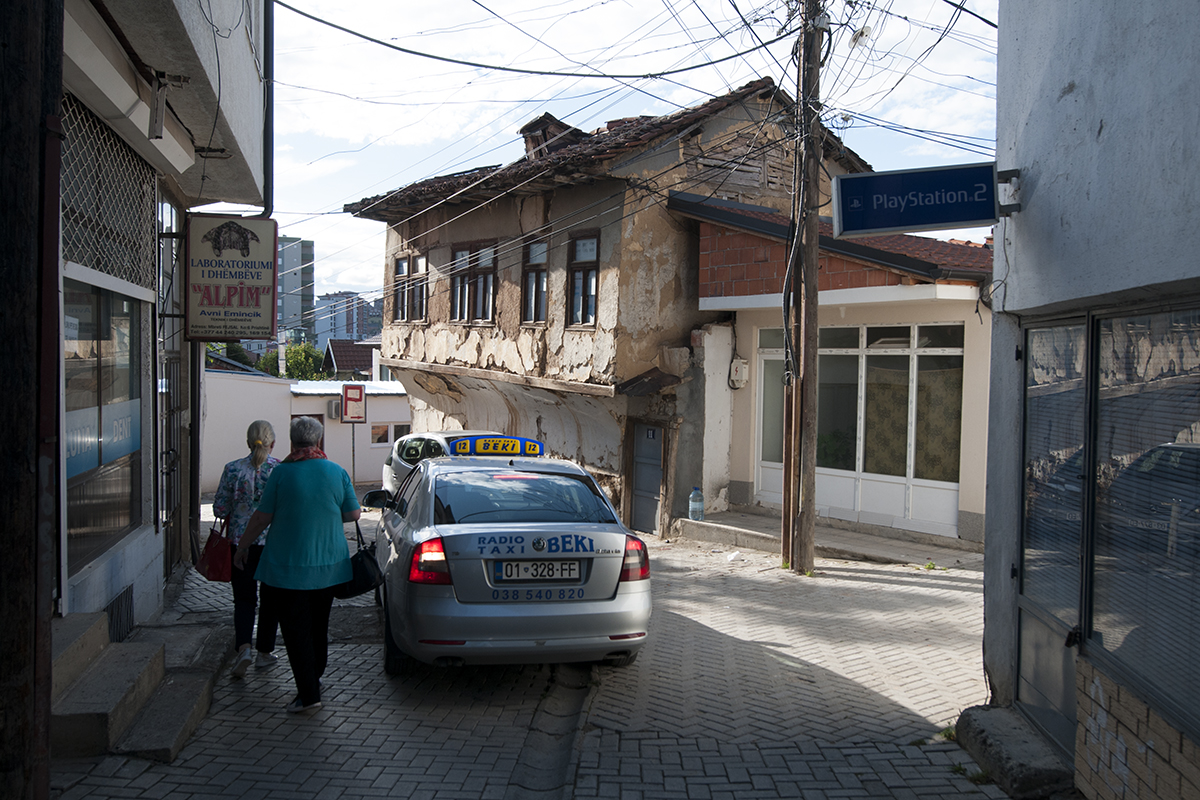 Two women walking past a taxi doing a u-turn in a small street of Pristina