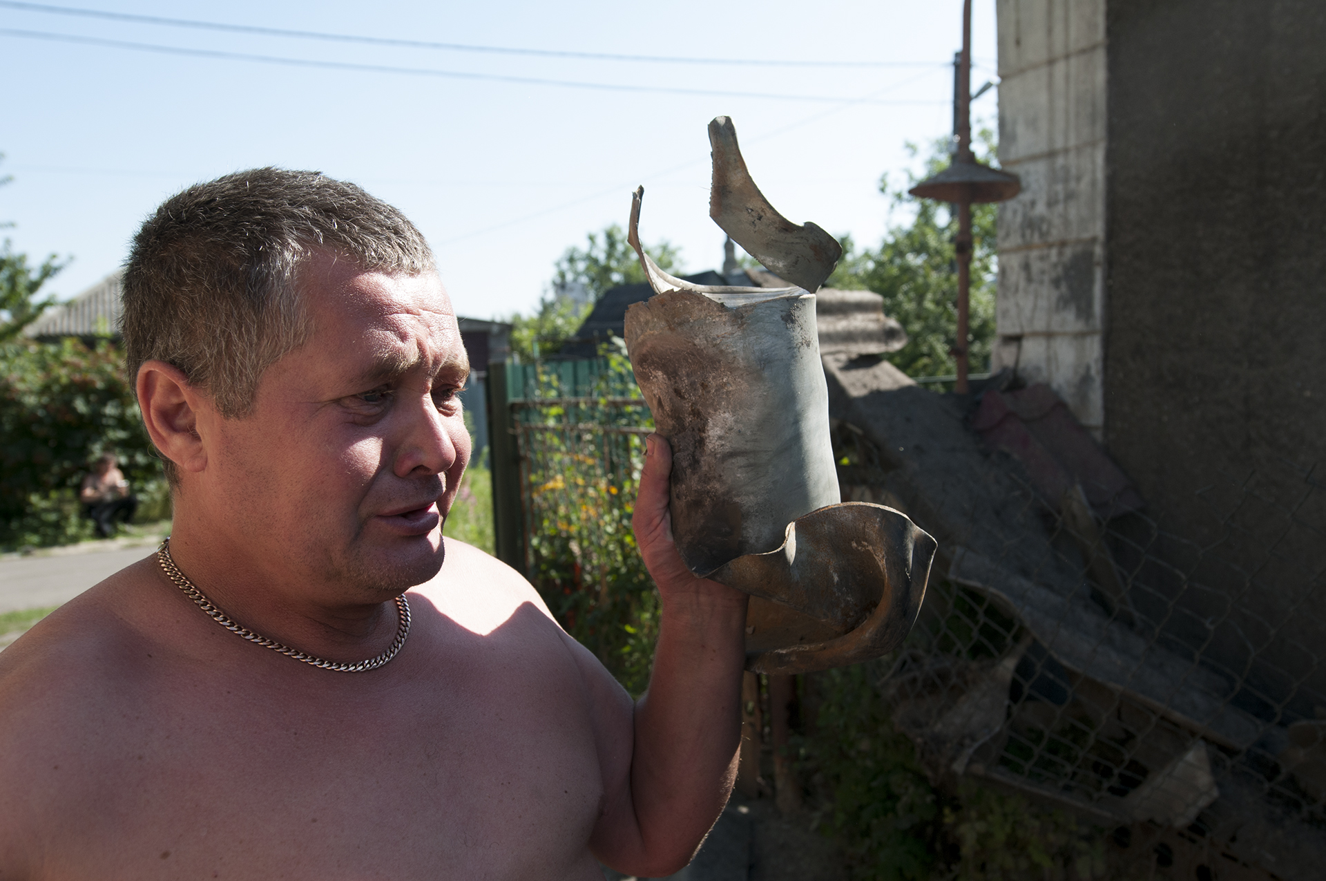 A man holding a piece of the GRAD rocket that has just destroyed his home