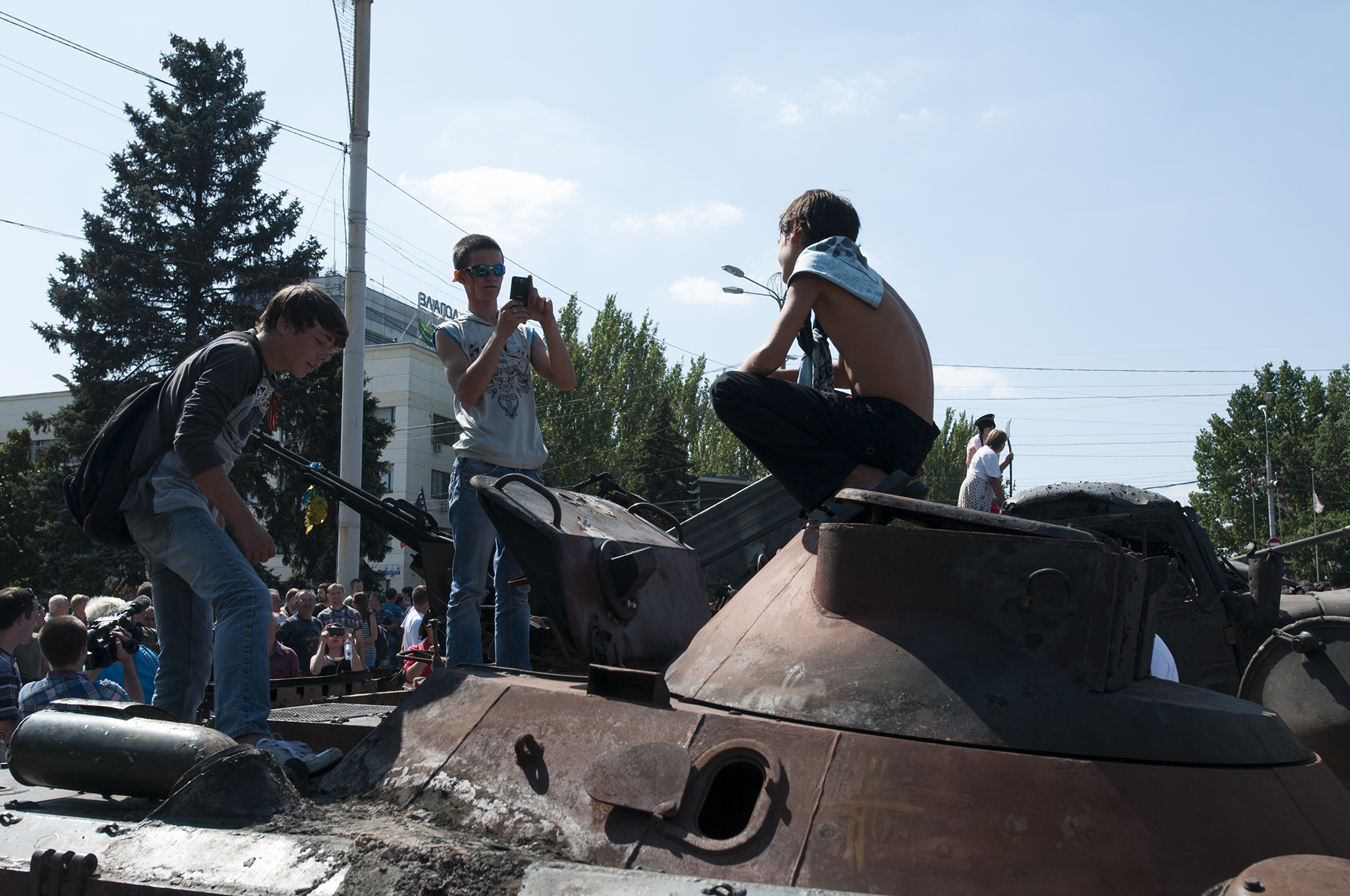 Kids taking pictures on top of a destroyed Ukrainian BTR exposed on Lenin Square