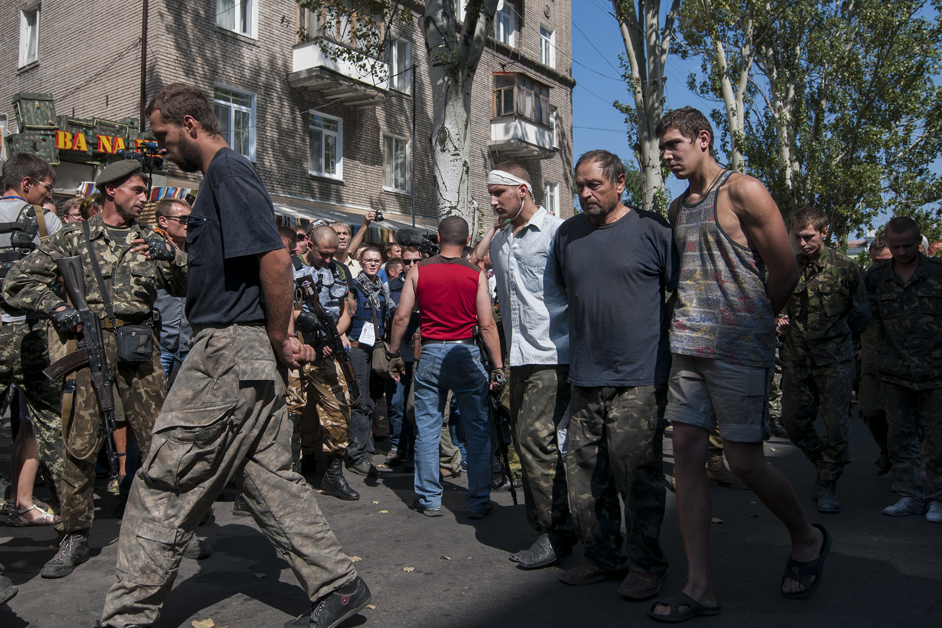 Ukrainian prisoners of war being escorted back to a bus after have been marched down the streets of Donetsk as war trophies