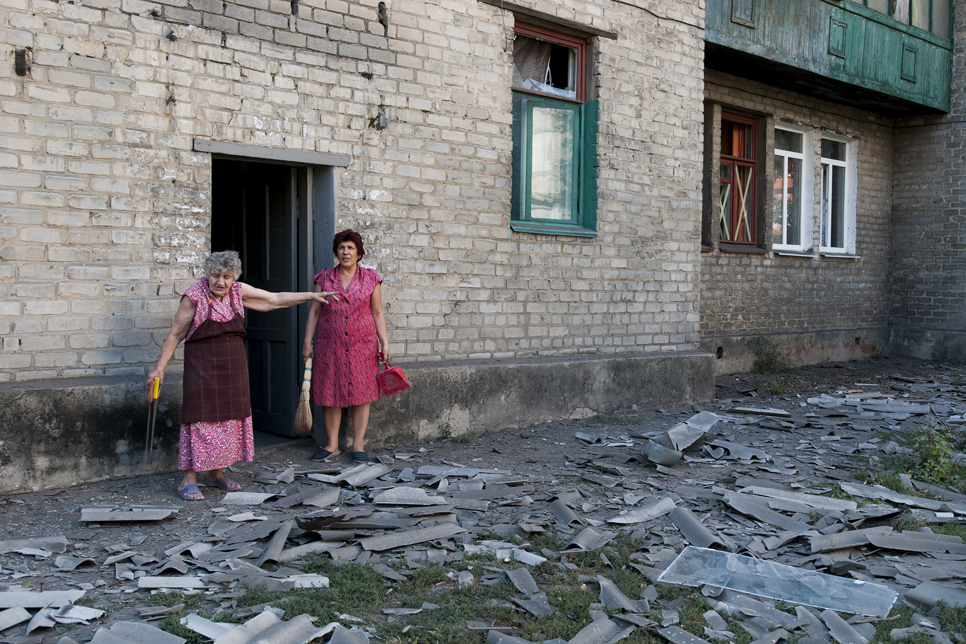 Local residents stand infront of the building where they live after a shelling in Donetsk