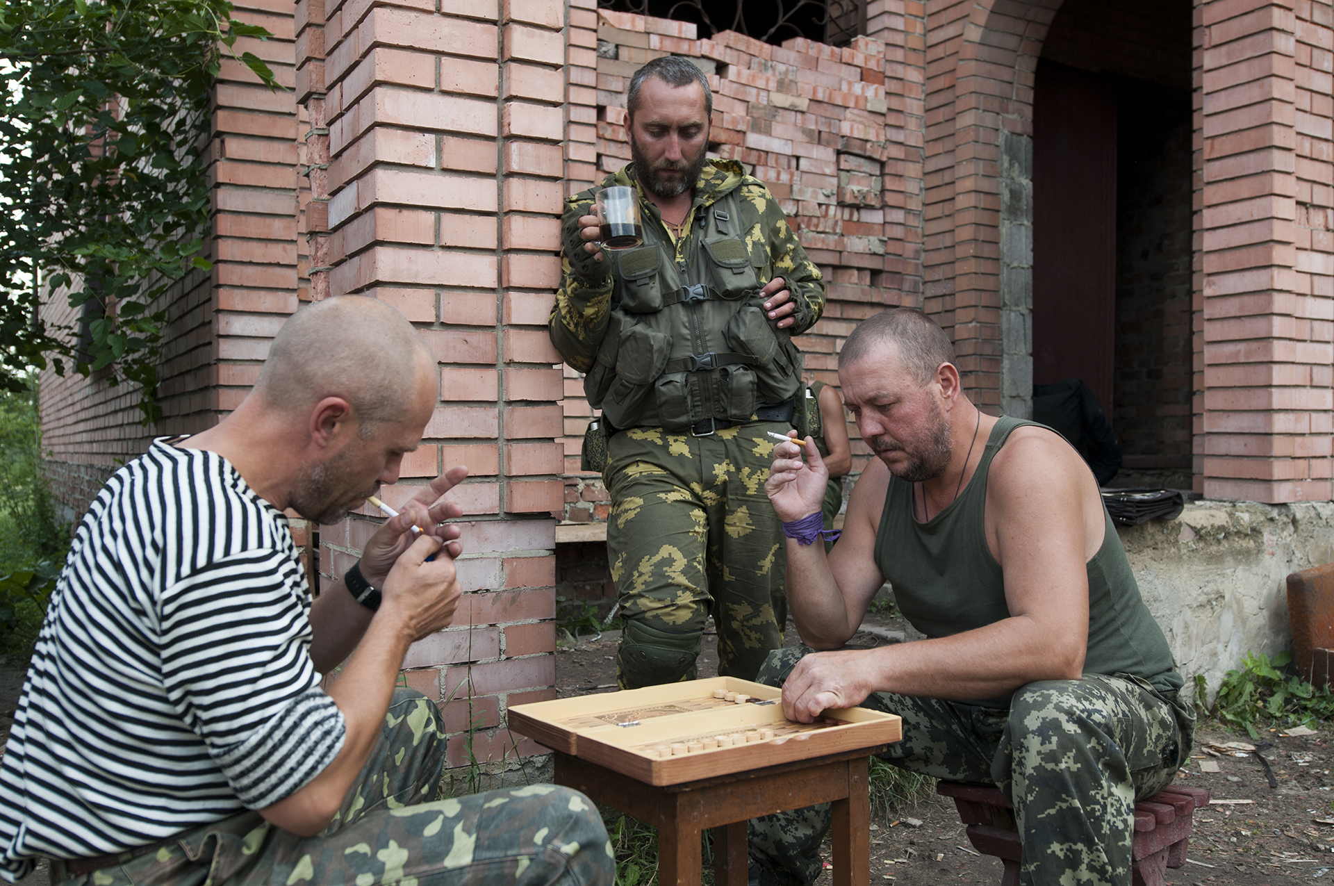 Fighters from the Patriot Battalion playing backgammon while smoking and having coffee on the front line