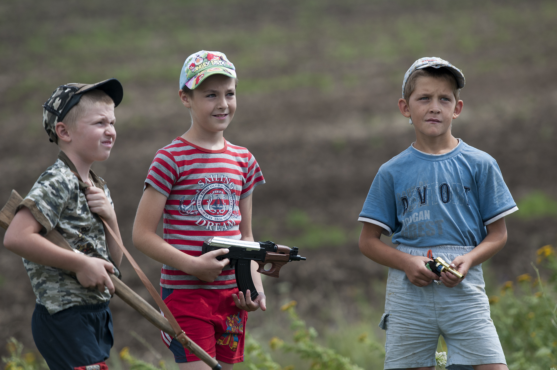 Local children holding toy guns stand at the MH17 crash site