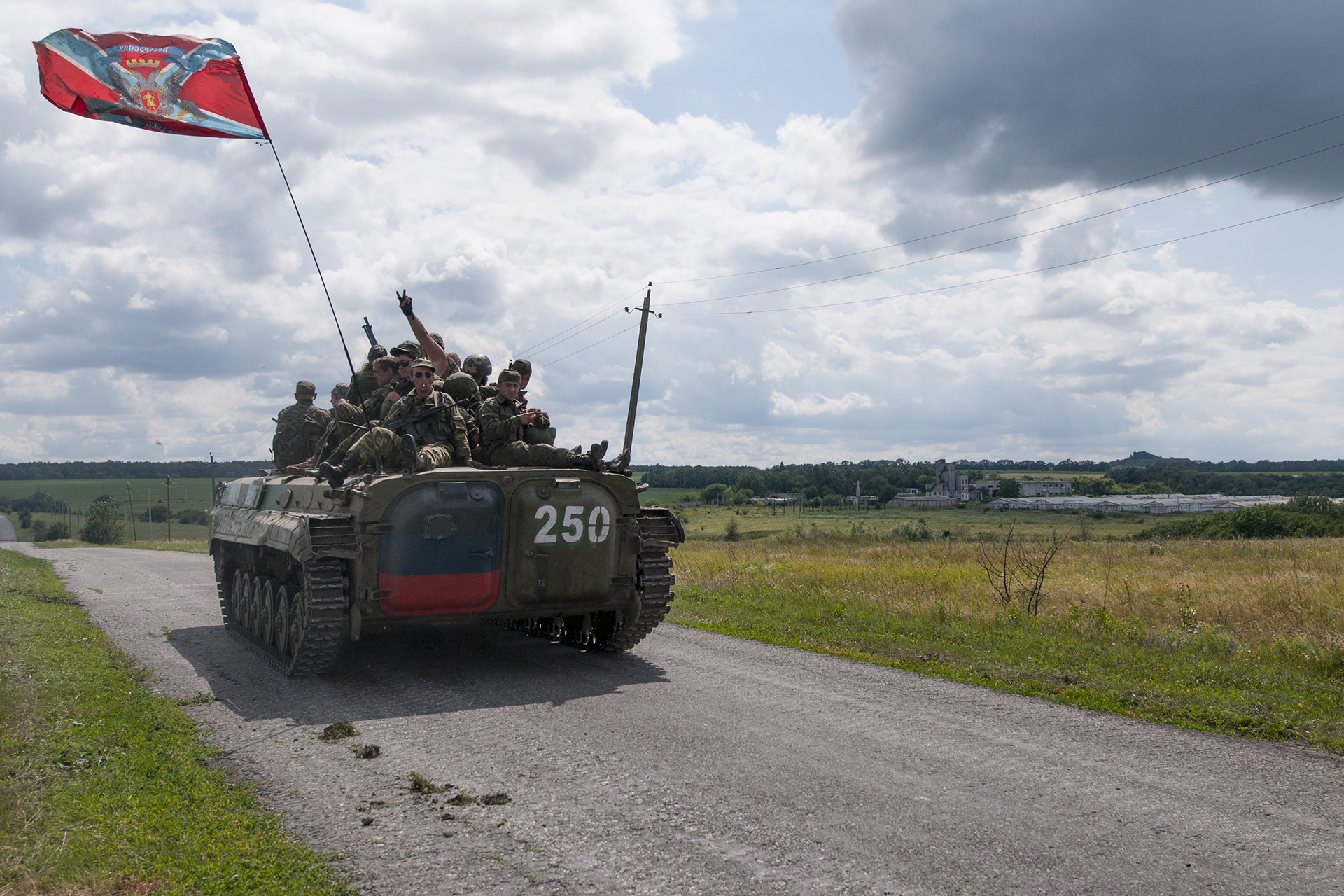 Russia-backed separatists sit atop an APC with a flag of the self-proclaimed Federal State of Novorossiya at the MH17 crash site a year after it was shot down