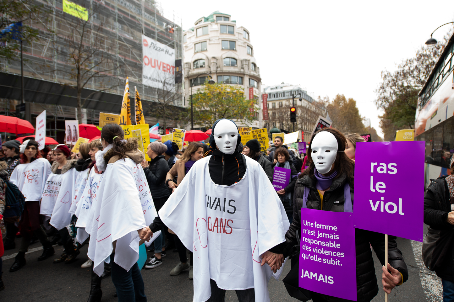 "Militant from  Les Masques Blancs  association carrying a sing saying ""A woman is never responsible for the violence she is subjected to. NEVER"" and an other one with ""enough of rape"" written on it."