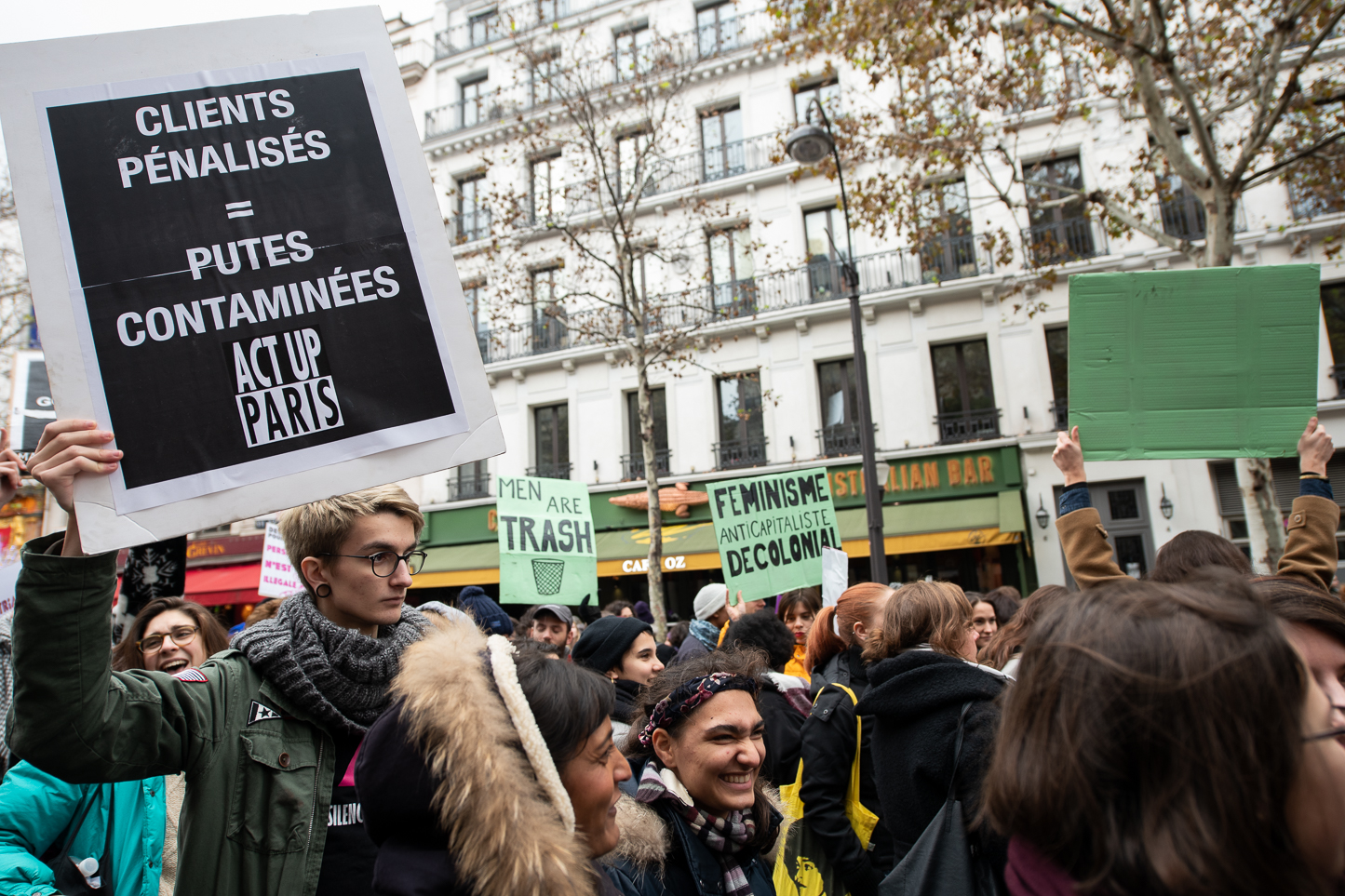 "A person holding a sign from the french association  Act Up Paris  fighting against HIV, ""penalized clients = infected whores""."