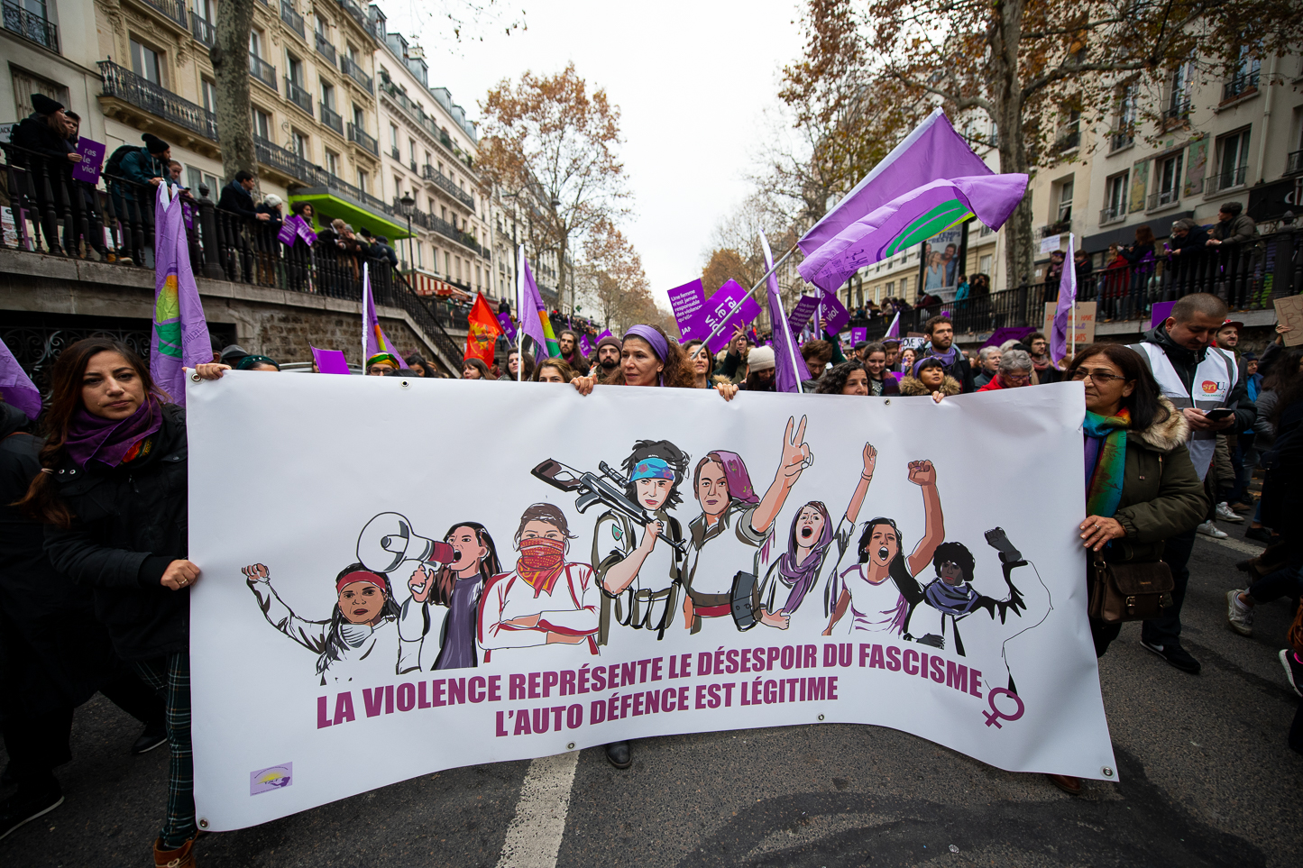 "Militants from the  Kurdish women's movement in France  holding a banner saying ""the violence represent the despair of fascism; self defense is legitimate"""