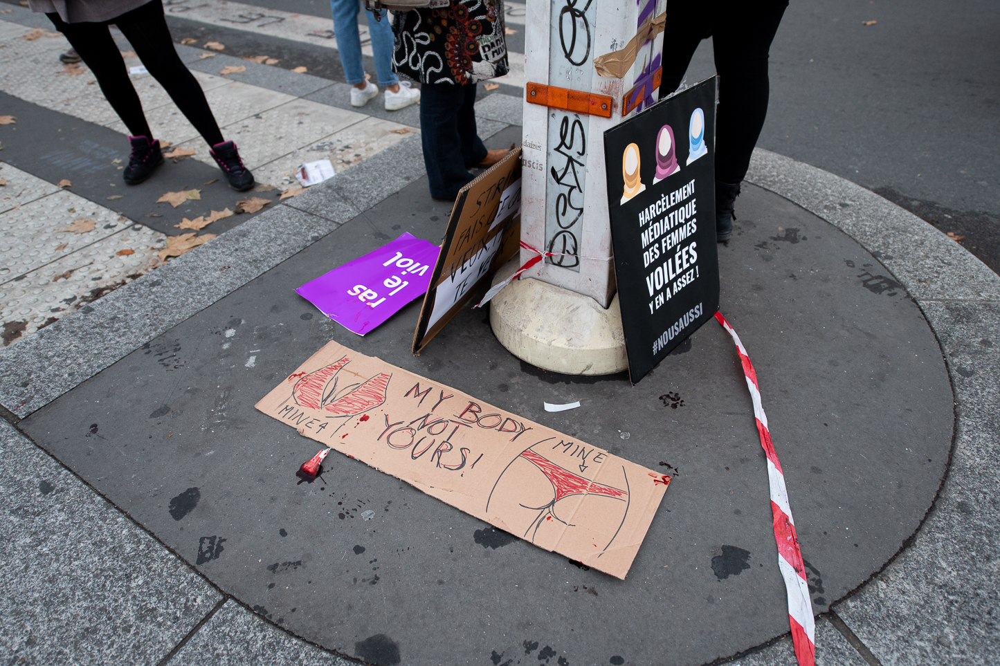 Tampon filled with fake blood alongside sings left on the ground at then end of the the march.