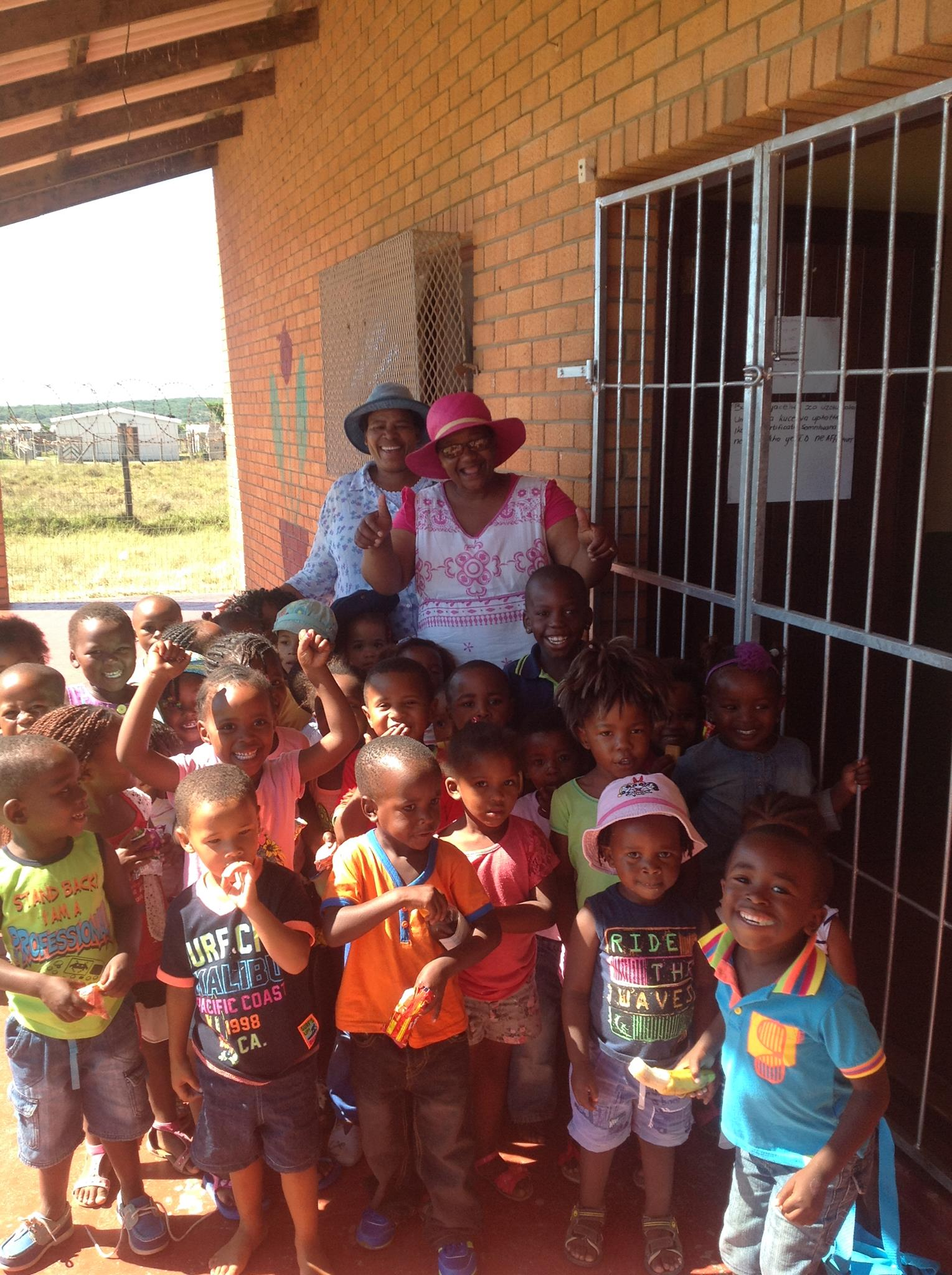 Mrs. Adams and the children of the Masibulele Preschool stand in front of their brand new security gate!