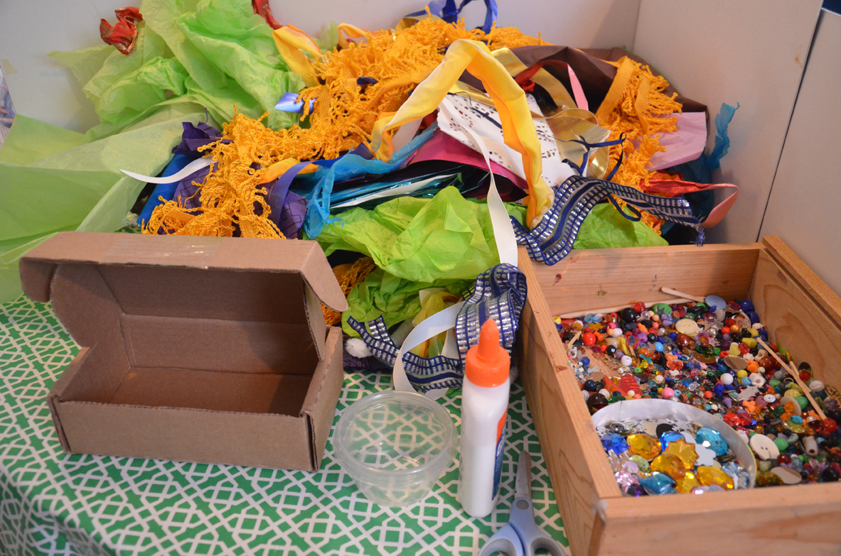 Assorted collage materials include tissue paper, ribbons, and beads.